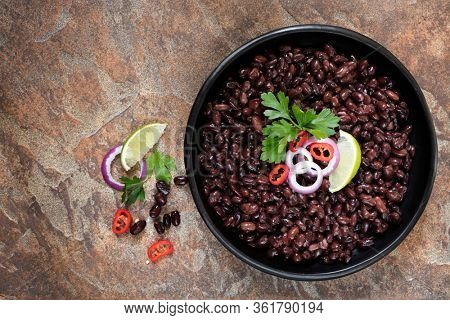 Black beans in rustic bowl over slate background