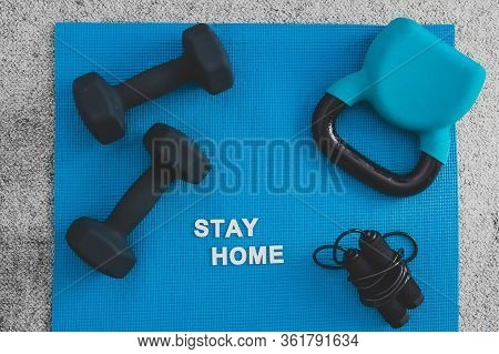 Social Distancing Against Covid-19 Virus, Stay Home Message Surrounded By Fitness Gear For Home Work