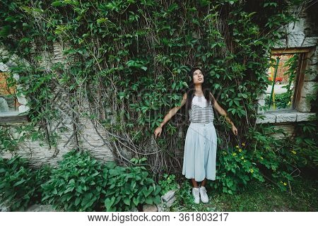 Lonely Girl In Garden Among Summer Greenery. Mad Country Girl Near Green Hedge In Spring Time. Beaut