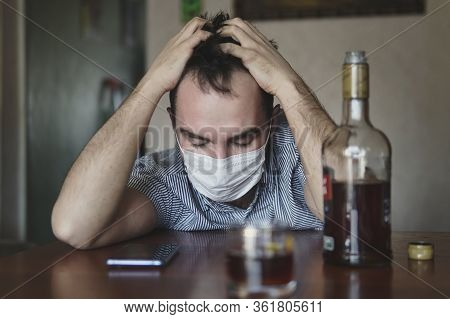 A Tired Sick Man In Sorrow Drinks Rum Alone. Man With Alcohol Wearing Medical Mask. Corona Virus Con