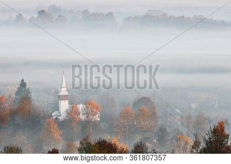 View Of Transylvanian Village In The Fog, Morning Image Taken In Romania