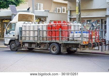 Truck With Gas Cylinders On The Road. Many Red And Gray Gas Cylinders Transported In Car. 19 August
