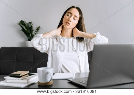 Tired Young Business Woman Or Student Using Laptop At The Home Office And Have A Neck Pain.