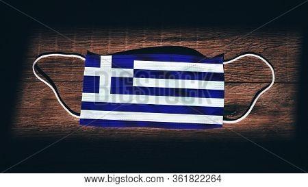 Greece National Flag At Medical, Surgical, Protection Mask On Black Wooden Background. Coronavirus C