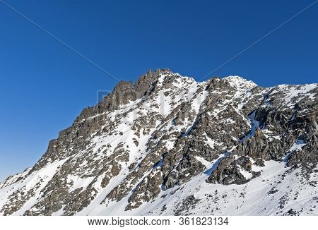 Rugged Alpine Rocky Mountainside Landscape Covered In Snow And Ice