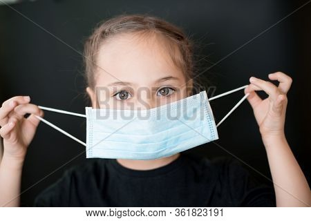 European Young Girl Puts On A Medical Mask. Conceptual Photo On The Theme Of The Covid-2019 Pandemic