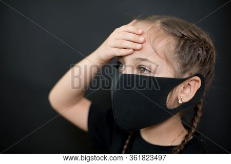 Young Girl In Protective Sterile Medical Mask On Her Face Has Heat Temperature, Hold Head With Hand