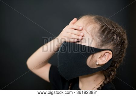 Young Girl In Protective Sterile Medical Mask On Her Face, Closes His Eyes With His Hand On A Black
