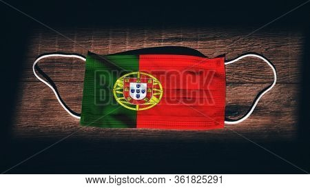 Portugal National Flag At Medical, Surgical, Protection Mask On Black Wooden Background. Coronavirus
