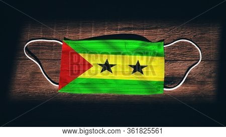 Sao Tome And Principe National Flag At Medical, Surgical, Protection Mask On Black Wooden Background