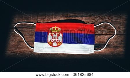 Serbia National Flag At Medical, Surgical, Protection Mask On Black Wooden Background. Coronavirus C