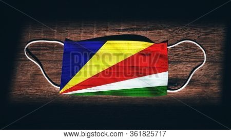 Seychelles National Flag At Medical, Surgical, Protection Mask On Black Wooden Background. Coronavir