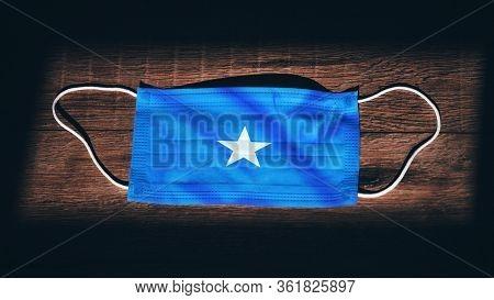 Somalia National Flag At Medical, Surgical, Protection Mask On Black Wooden Background. Coronavirus