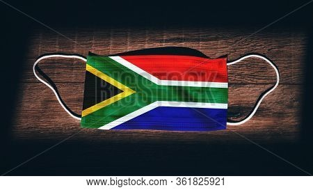 South Africa National Flag At Medical, Surgical, Protection Mask On Black Wooden Background. Coronav