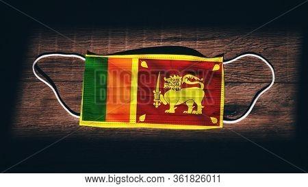 Sri Lanka National Flag At Medical, Surgical, Protection Mask On Black Wooden Background. Coronaviru