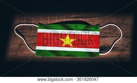 Suriname National Flag At Medical, Surgical, Protection Mask On Black Wooden Background. Coronavirus