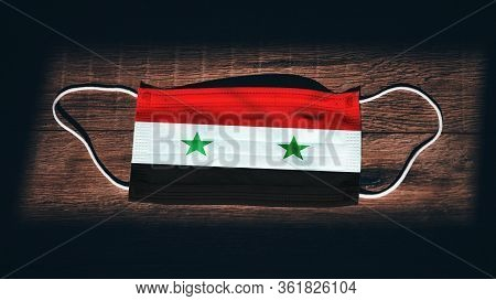 Syria National Flag At Medical, Surgical, Protection Mask On Black Wooden Background. Coronavirus Co