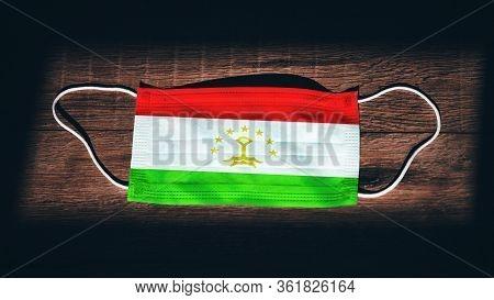 Tajikistan National Flag At Medical, Surgical, Protection Mask On Black Wooden Background. Coronavir