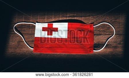 Tonga National Flag At Medical, Surgical, Protection Mask On Black Wooden Background. Coronavirus Co