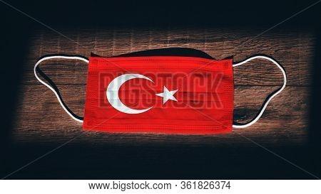 Turkey National Flag At Medical, Surgical, Protection Mask On Black Wooden Background. Coronavirus C