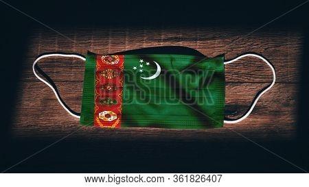 Turkmenistan National Flag At Medical, Surgical, Protection Mask On Black Wooden Background. Coronav