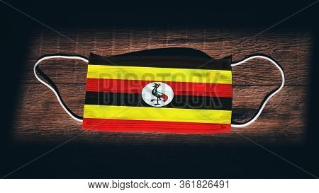 Uganda National Flag At Medical, Surgical, Protection Mask On Black Wooden Background. Coronavirus C