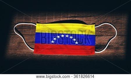 Venezuela National Flag At Medical, Surgical, Protection Mask On Black Wooden Background. Coronaviru