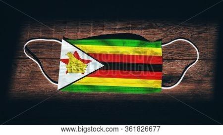 Zimbabwe National Flag At Medical, Surgical, Protection Mask On Black Wooden Background. Coronavirus