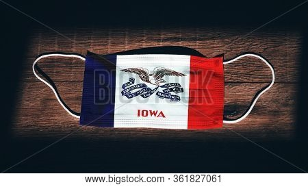 Iowa Flag. Coronavirus Covid 19 In U.s. State. Medical Mask Isolate On A Black Background. Face And