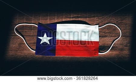 Texas Flag. Coronavirus Covid 19 In U.s. State. Medical Mask Isolate On A Black Background. Face And