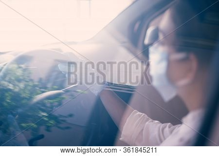 A Young Woman In A Surgical Face Mask And Gloves Driving The Car During Coronavirus Pandemic. A Fema