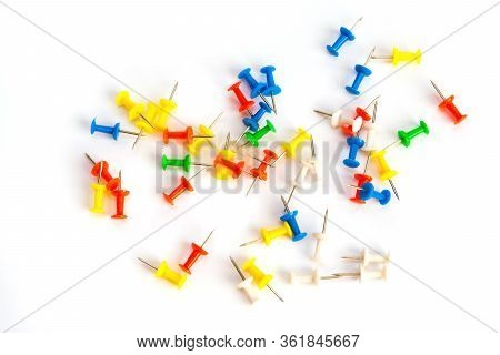 Multi-colored Pushpins Scattered Over A White Background. Top View