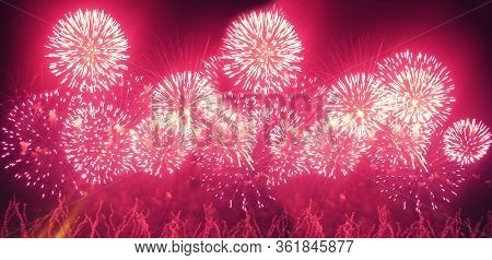Fireworks Display On Dark Sky Background. Flashes Of Red And White Fireworks Against The Night Black