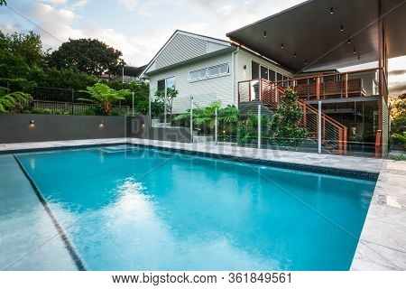 Modern Pool Close Up With Light Blue Water And Large And Beside A Mansion With A Beautiful Garden Wi