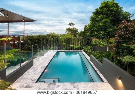 Modern Hotel With A Pool Under The Bright Blue Sky With White Clouds Beautifully Spread. There Is Lo