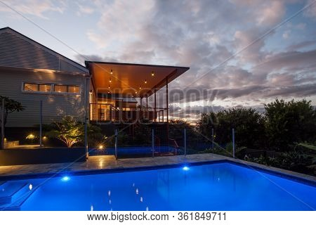 Modern Hotel Or House With A Dark Blue Water Swimming  Pool At Night With Lighter Sky And Clouds,  T