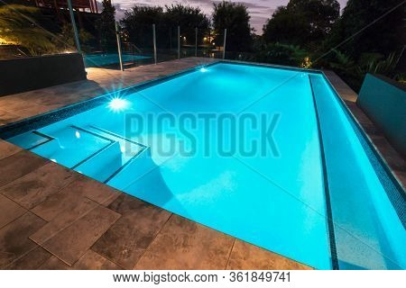 Blue Water Swimming Pool With Flashing Lights With Floor Tiles Surrounded By Dark Trees In A Garden