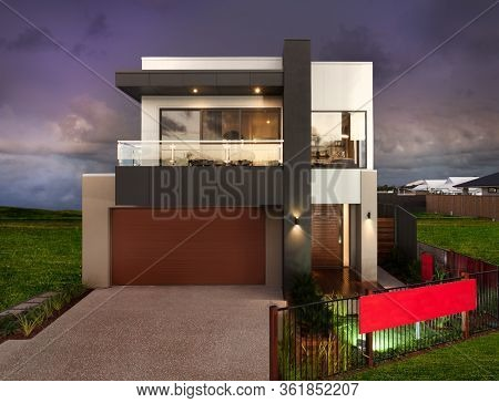 Luxury House With A Green Grass Lawn With A Fence Around And The Sky Is Dark And Purple, There Is A