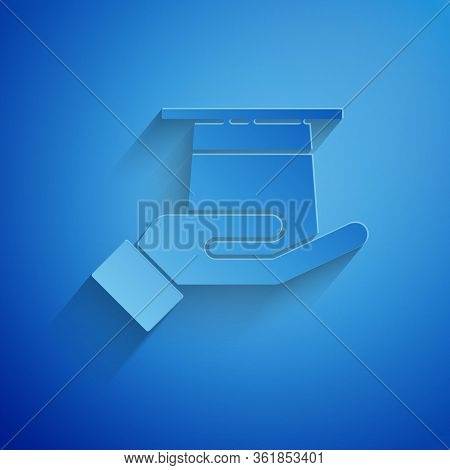 Paper Cut Magician Hat In Hand Icon Isolated On Blue Background. Magic Trick. Mystery Entertainment