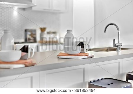 Kitchen Counter Top Closes Up With A Tap And Mug With Napkins Near White Bottles, The Background Is