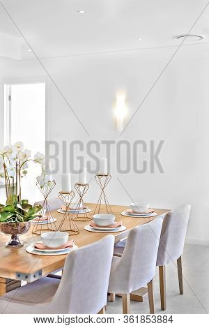 Dining Area With A Wooden Table And Chairs In A Room With White Walls, There Is A Door  Which Spread