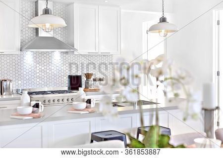 Modern Kitchen With White Decoration And Kitchenware Including Hanging Lamps, Pantry Cupboards And C