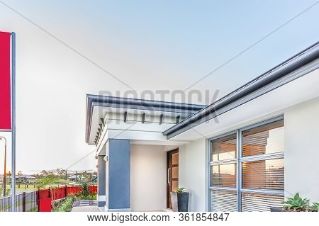 Modern House Or Hotel Front Side With A Fence, There Are Houses And Green Grass Ground From The Dist