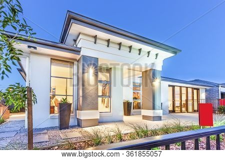 Luxury House Facade Over The Metal Fence Under Blue Sky, There Are Trees And Gravel On The Ground Of