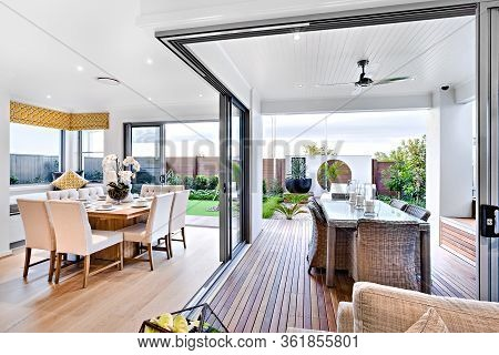Modern Dining Room Attached To Outside Patio Area With A Garden Including A Green Lawn And Vase, The