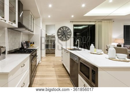 Luxury Kitchen Through The Hallway To A Another Room Between Stoves, Oven, Countertop And Cupboards