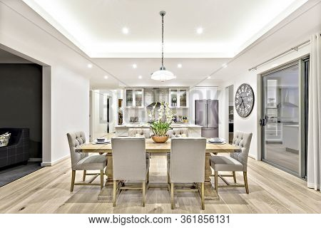 Modern Dining Room With Hanging Lamps On, There Are Chairs And Table Setup With Fancy Items On The W