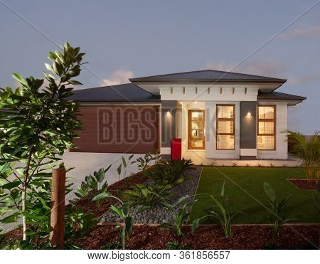 Modern House Or Hotel With A Green Lawn Garden Including Plants And Gravel Ground Illuminated At Nig