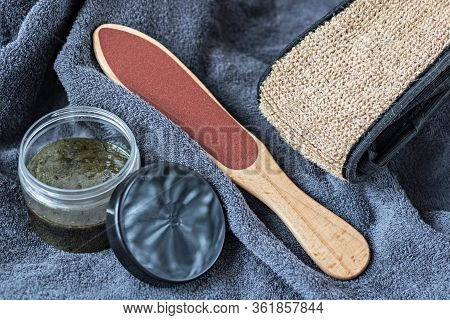 On The Gray Background Of A Terry Towel Are Pedicure Supplies: A Rough Washcloth, Scrub And Foot Fil