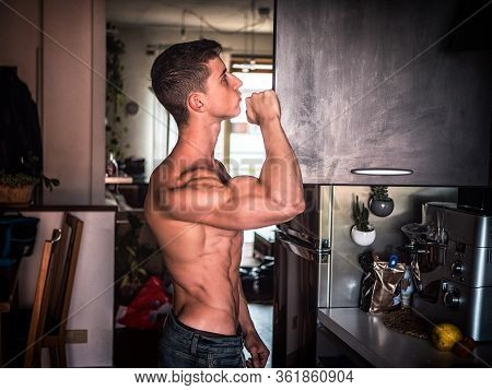 Young Bodybuilder Looking For Food In Kitchen Cupboard